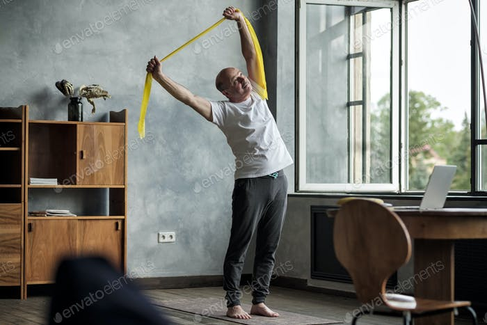 Hispanic man doing side bend exercise using resistance band practicing alone