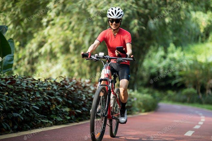 Frau Biker mit Smartphone Reiten im Park