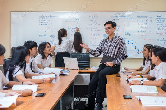 Asian teacher Giving Lesson to group of College Students in the classroom