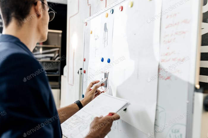The architect dressed in blue checkered jacket attaches blueprints to a magnetic board on the wall