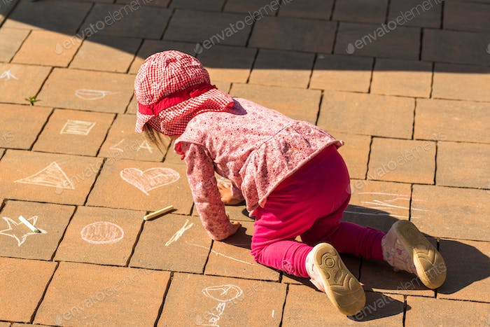 Focused child drawing on on stone tiles with chalk outdoors