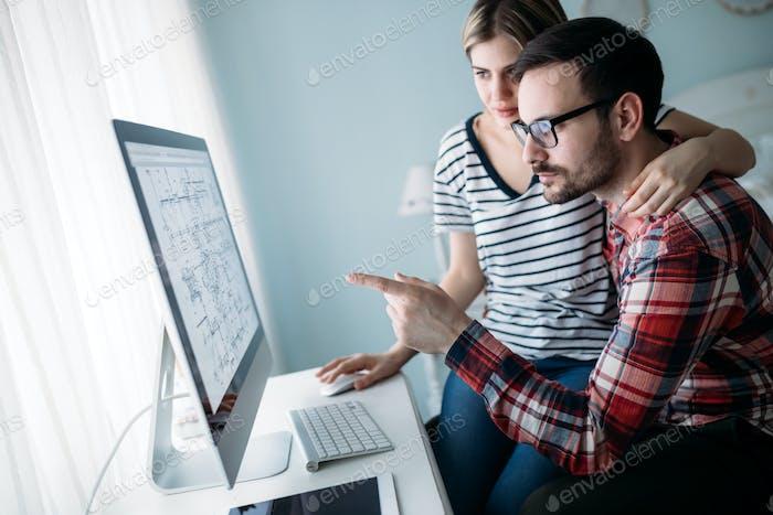 Junge attraktive Designer, die gemeinsam an Projekt arbeiten