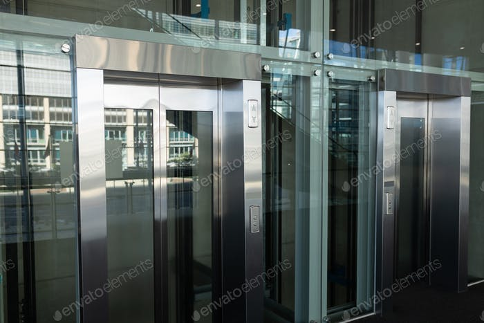 Side view of two modern elevators in a workplace