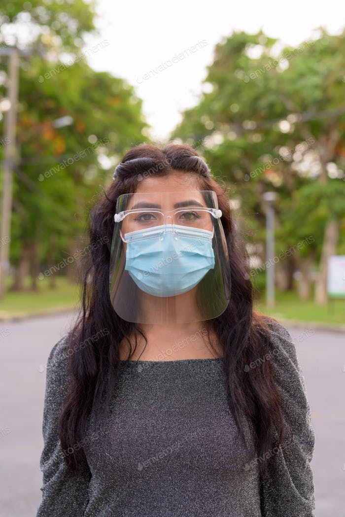 Young Indian woman wearing mask and face shield at the park outdoors