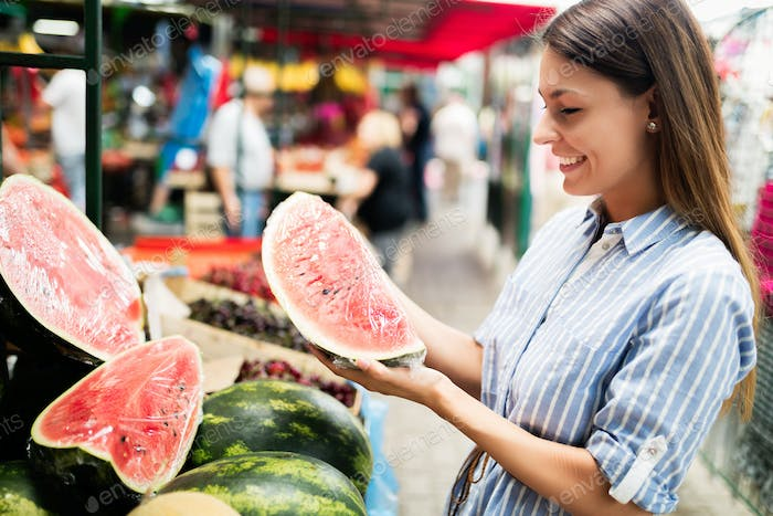 Beautiful young brunette woman on a market getting food.