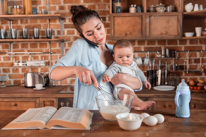 Young mother holding her son, talking on smartphone and mixing a dough at the kitchen. family life
