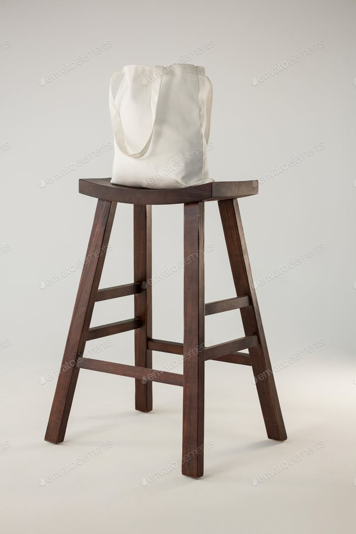 White bag on wooden stool