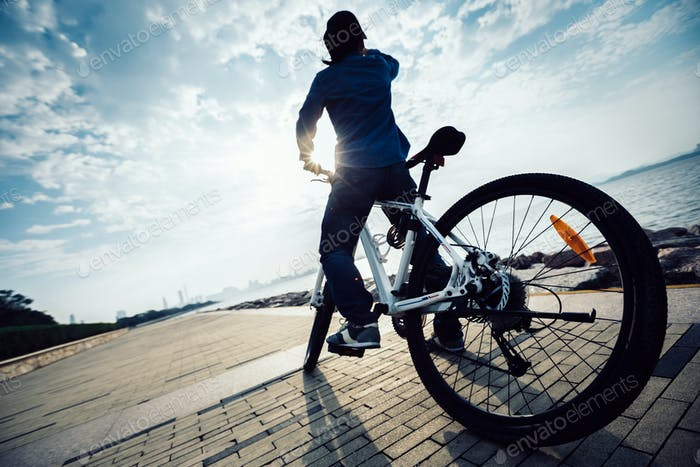 Cyclist looking at the sunrise on seaside