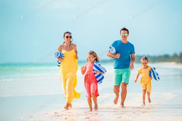 Happy beautiful family of four on the beach