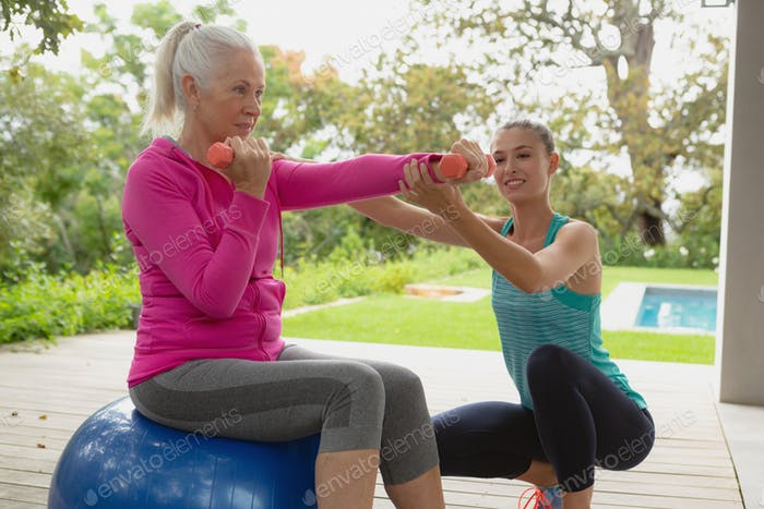 Beautiful Caucasian female trainer assisting active senior Caucasian woman to exercise