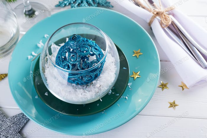 Christmas table setting with toy ball and decoration on white wooden table