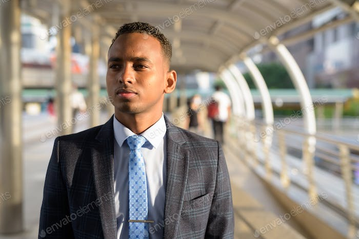 Young handsome African businessman wearing suit thinking in the city