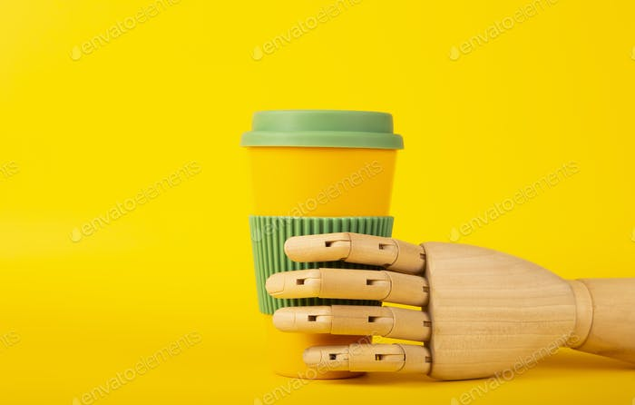 Wooden mannequin hand holding reusable coffee cup on a yellow background with space for text