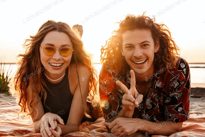 Young loving couple lying at the beach and showing peace