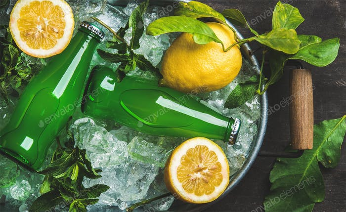 Bottles of green lemonade on chipped ice in metal tray