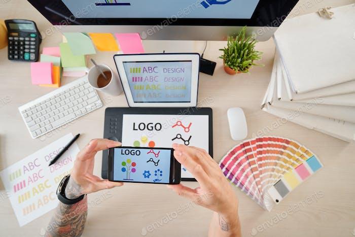 Designer photographing logotype