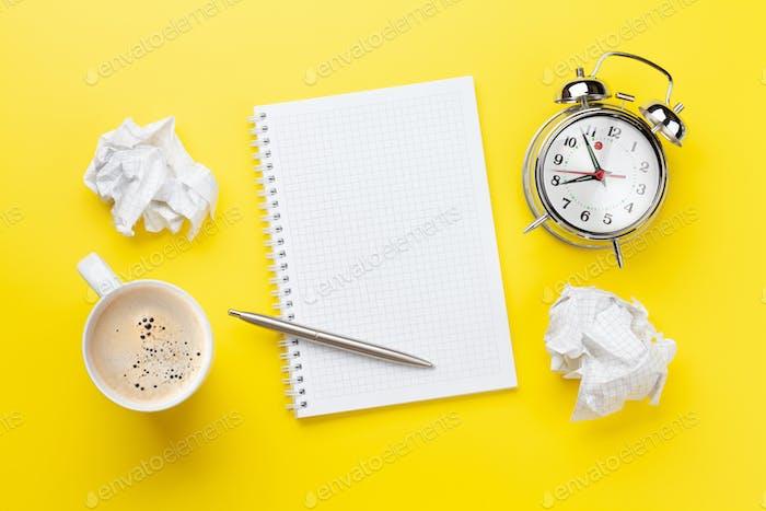 Bürotisch mit Kaffee, Wecker und leerem Notizblock