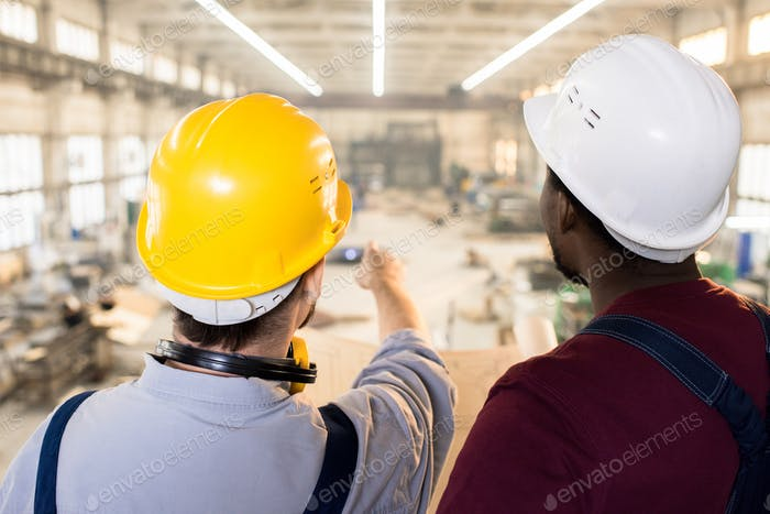 Skilled engineers visualizing sketch at construction site