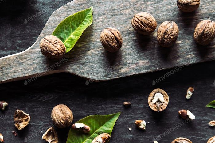 Walnüsse auf dunklem Vintage-Tisch. gesundes Essen. Alter Vintage Tisch und Blätter aus der Nuss