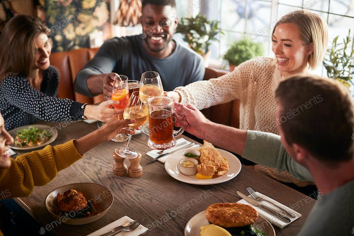 Friends Meeting For Meal In Traditional English Pub Making Toast Together