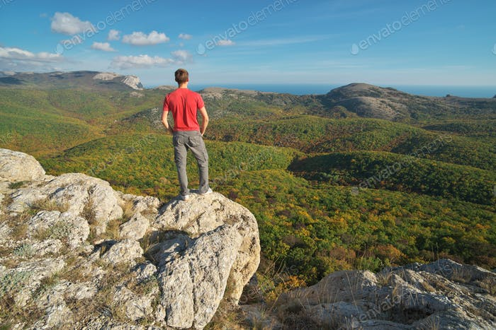 Man standing on the edge of cliff mountain.