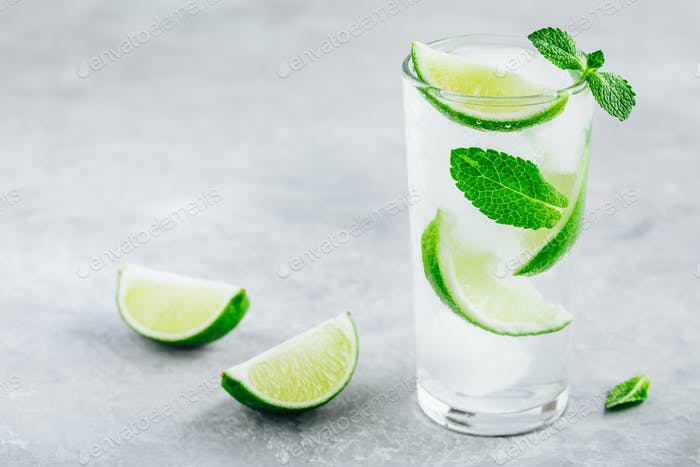 Mojito cocktail with ice, fresh mint and lime in glass on gray stone background.