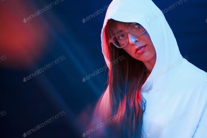 Caucasian ethnicity. Studio shot in dark studio with neon light. Portrait of young girl