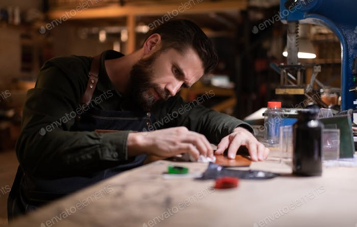 Artisan frowning and working with leather