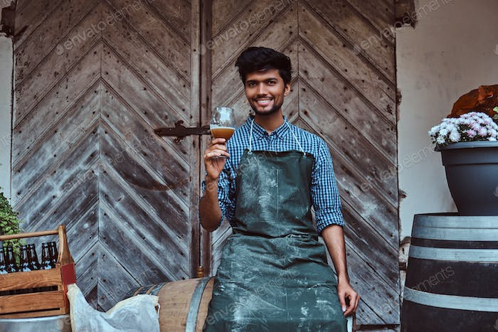 Brewmaster sitting on wooden barrel and holds a glass of craft beer relaxes after work.