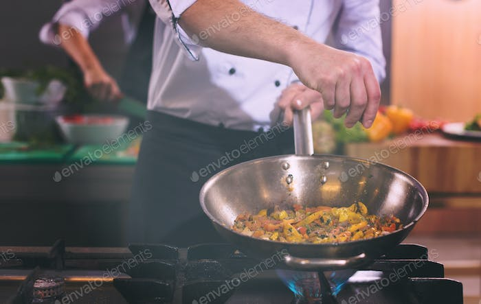 chef putting spices on vegetables in wok