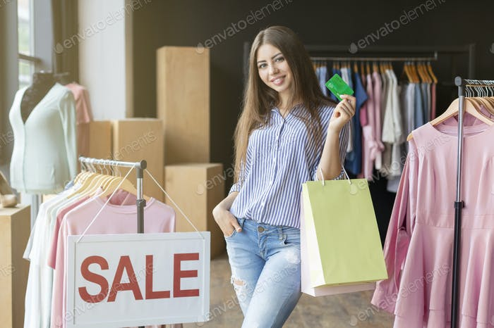Cheerful young woman holding purchases and recommending credit card