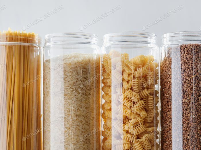 Various pasta and cereal grains in plastic jars for a long storage.