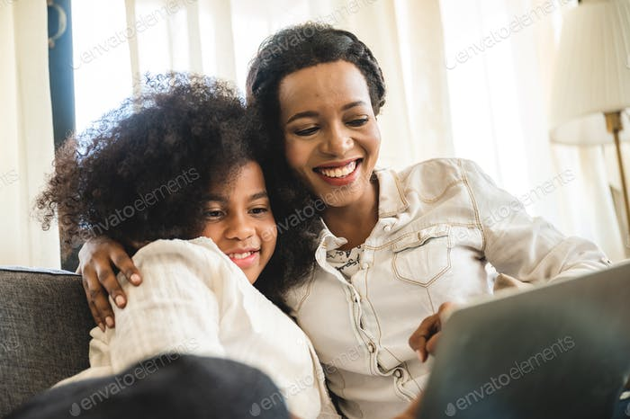 African American children watching on laptop, education at home with mom
