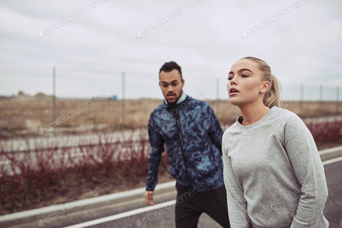 Young couple catching their breath while out for a jog