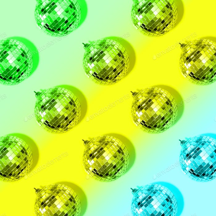 New year baubles. Shiny gold disco balls on neon background. Pop disco style attributes, retro