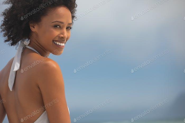 Frau lächelnd am Strand und Blick in die Kamera an einem sonnigen Tag