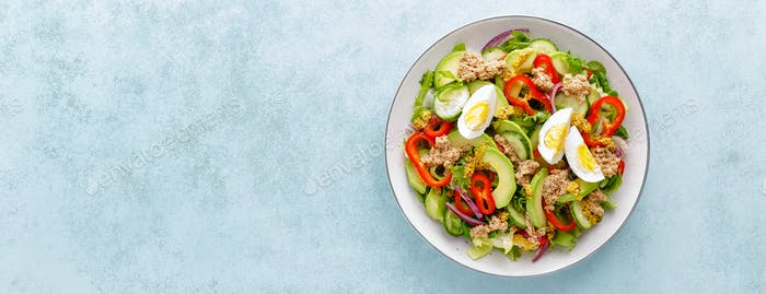 Tuna salad with boiled egg and fresh vegetables. Healthy diet food. Greek cuisine. Top view. Banner