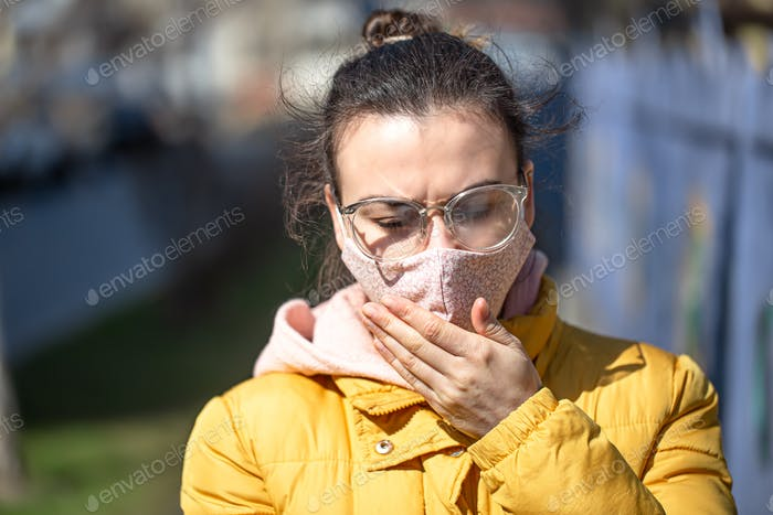 A young woman in a mask during the pandemic. Coronavirus.