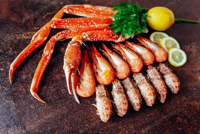 Zusammensetzung mit Krabben, Garnelen, Kräutern und Zitrone auf einem roten Hintergrund