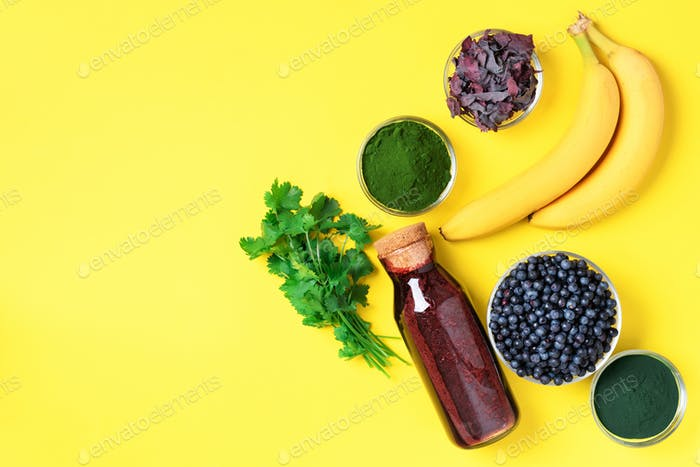Blueberries, bilberry, barley grass, spirulina, orange juice, dulse, cilantro on yellow background