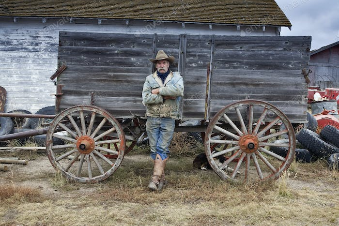 Man in cowboy hat and cowboy boots leaning against a wooden wagon.