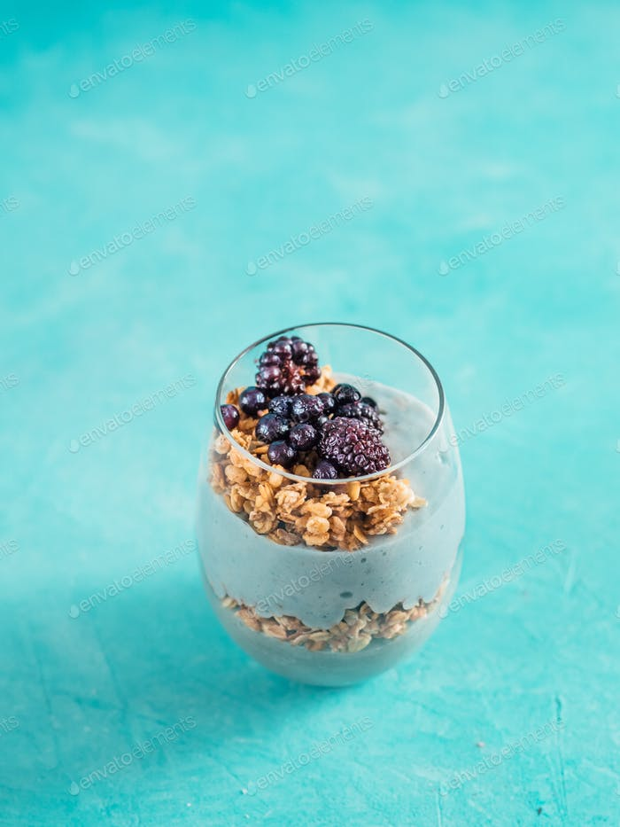Spirulina smoothie and granola on blue tabletop