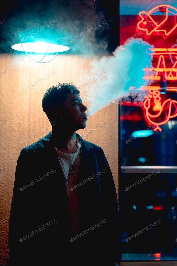 Hombre fuma cigarrillo Electrónico bajo la linterna, mirando hacia otro Lejos
