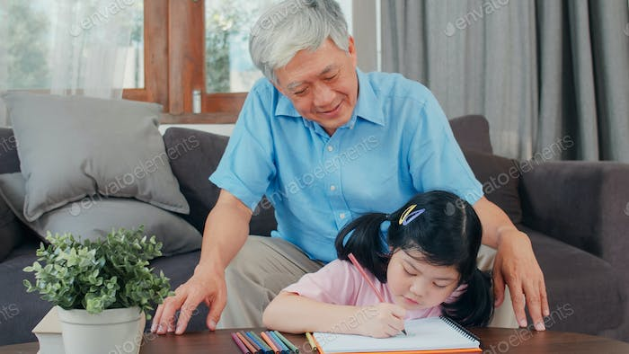 Asian grandfather teach granddaughter drawing and doing homework at home