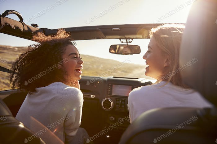 Two girlfriends driving with sunroof open look at each other