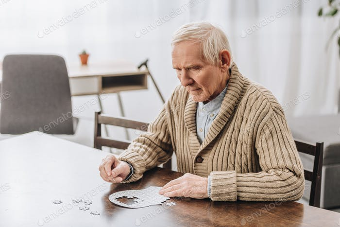 pensioner with grey hair playing with puzzles at home