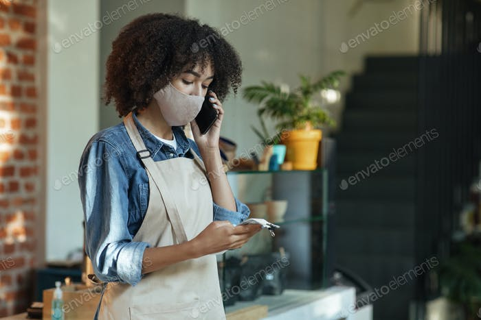 Concentrado afroamericano gerente administrativo de café en máscara protectora hacer revisiones después de