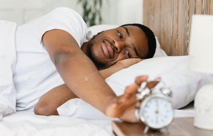 Wellslept Black Man Turning Off Alarm-Clock Waking Up In Bedroom