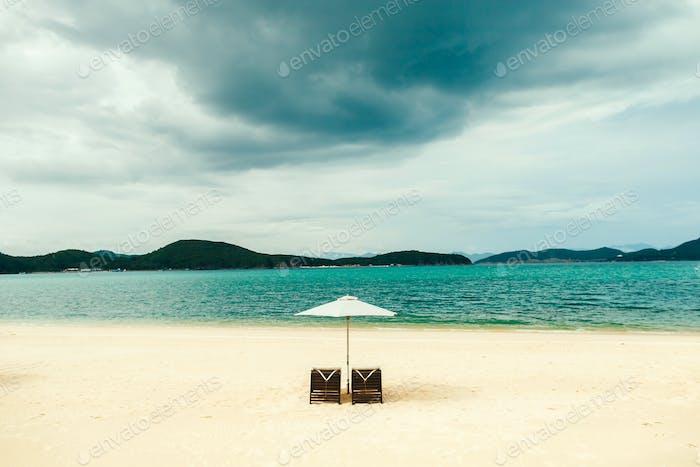 white sand beach resort with umbrella and sunbed