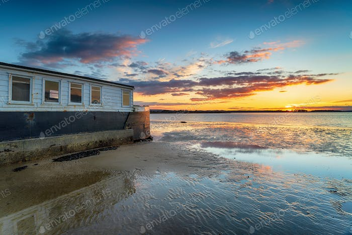 Sunset over an old boat on Bramble Bush Bay at Studland in Poole Harbour